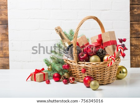 Christmas basket with champagne bottle and glasses, gifts with red satin ribbon, candy canes, pine cones, golden garlands on white brick wall background, new year celebration concept