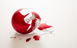 Christmas bauble broken isolated on white background, closeup view. Red xmas ball crashed in pieces. Holiday accident, fragility, anger concept