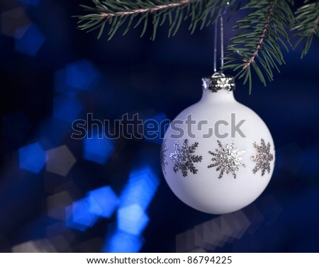 Christmas bauble hanging on fir branch in dark blurry back