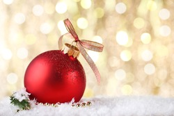 Christmas bauble with ribbon bow on blurred background