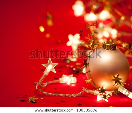 Christmas bauble with star-shaped lights and tinsel on red background