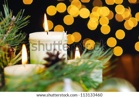 Christmas baubles and candle on black background of defocused golden lights.