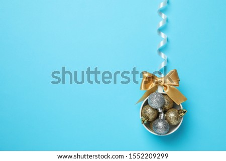 Christmas baubles and golden bow on blue background, space for text #1552209299