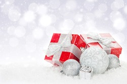 Christmas baubles and red gift boxes over snow bokeh background with copy space