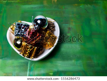 Christmas baubles in a heart shaped bowl on a green background  #1556286473