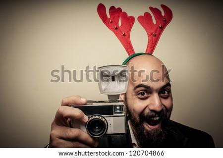 christmas bearded man holding old camera on grey background