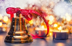 Christmas bell with red ribbon candles and snowy background. Happy christmas text on red ribbon.