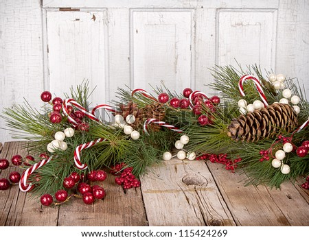 Christmas berries, Candy canes and pine branches on wooden background