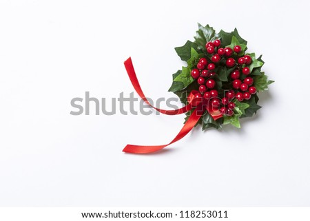 Christmas Berries garland with red ribbon and green leaves over white background.