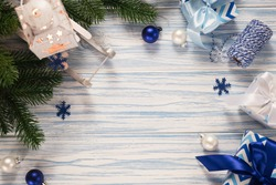 Christmas blue wooden background with fir tree, gift boxes, latern and decorative sleigh.
