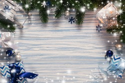 Christmas blue wooden background with fir tree, gift boxes, latern and decorative sleigh. View with copy space