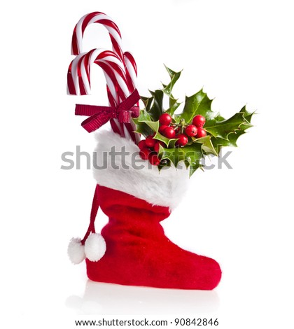 christmas boot stocking  filled  gifts ,sprig Christmas tree holly and  lollipop stick  isolated  on white background