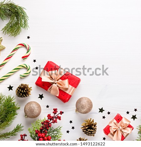 Christmas border flat lay with pine, presents, golden elements, candy canes, confetti. Christmas template on light wood