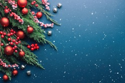 Christmas border with fir branches and red decorations on blue background with snow.
