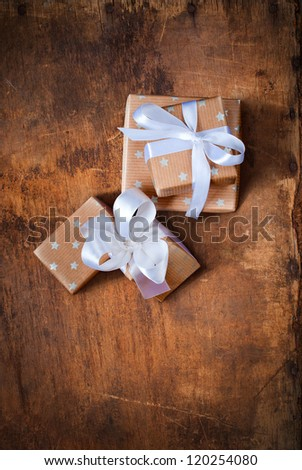 Christmas Boxes with White Ribbon on a Wooden Surface