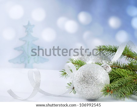 Christmas branch of tree ribbon and bauble against snow background creative concept #106992545