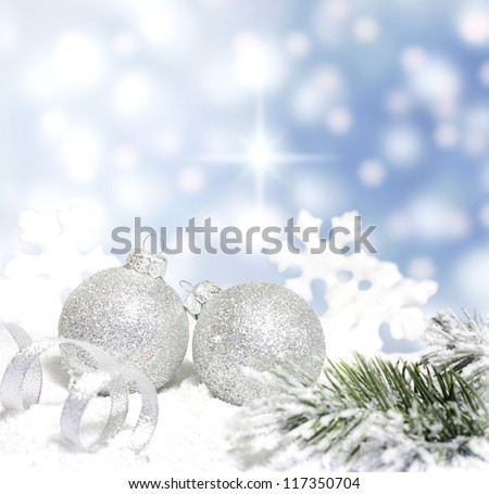 Christmas branch of tree ribbon silver baubles and snow on blue background #117350704