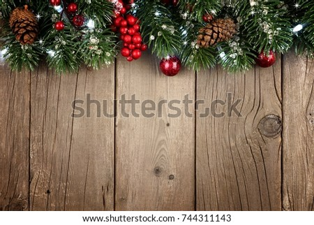 Christmas Branch Top Border With Berries And Pine Cones On A Rustic Old Wood Background