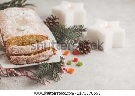 Christmas bread with candied fruits and powdered sugar in Christmas decorations, copy space.