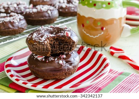 Christmas breakfast table with double chocolate peppermint donuts sitting on red and white striped plate with hot cocoa in gingerbread man mug #342342137