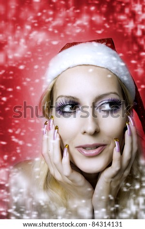 Christmas bright make-up and long nails manicure concept. Portrait of young woman model at santa hat, face closeup