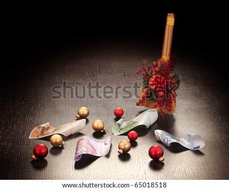 Christmas business decoration: euros swept with broom on dark background.