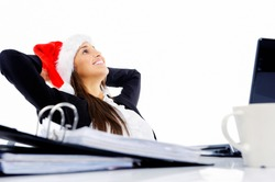Christmas business woman daydreaming at her desk isolated on white background