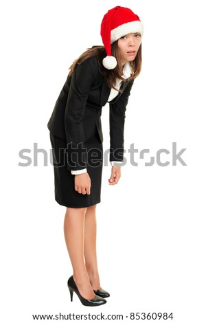 Christmas business woman tired wearing santa hat standing bored bending over. Christmas business concept of businesswoman stressed and exhausted isolated in full body on white background. - stock photo
