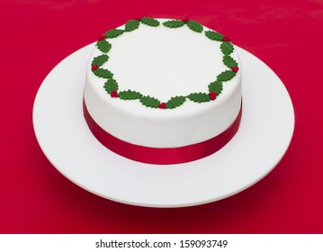 A stock photo of a Christmas cake on a red background