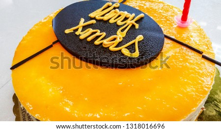 """Christmas cake, tastefully decorated, as a catering concept. A handmade specimen. The words """"Merry Xmas"""" written on top of the cake using yellow color cream. #1318016696"""