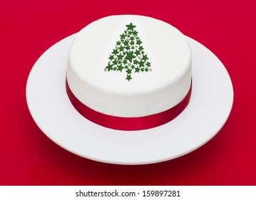 A stock photo of a Christmas cake with a Christmas tree decoration on a red background