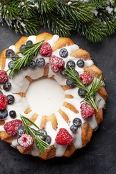 Christmas cake with berries and rosemary. Top view flat lay with copy space