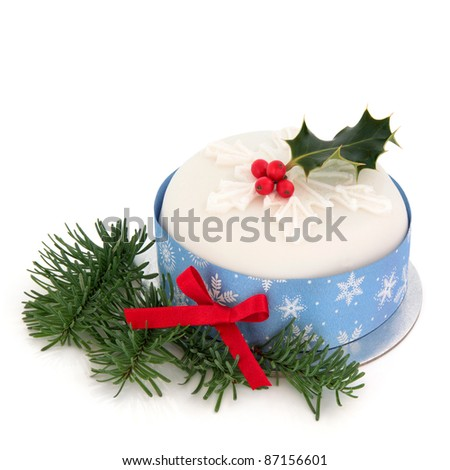 Christmas cake with icing sugar snowflake design and holly with ribbon band on a circular silver tray with spruce pine fir leaf sprigs isolated over white background.