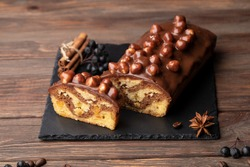 Christmas cake with nuts, biscuit Chocolate Christmas Cake on white plate. Traditional New Year dessert. Copy space.