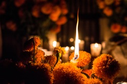 Christmas candle among flowers day of the dead, Janitzio Michoacan cemetery. Cempasuchil flowers