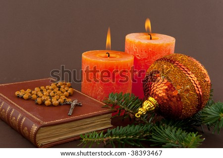 christmas candle and bible with rosary on brown