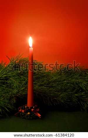 Christmas candle and pine branches. - stock photo