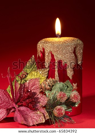 Christmas candle and poinsettia on red.
