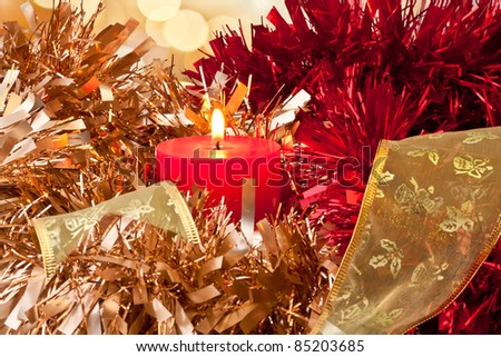 Christmas Candle burning surrounded by golden, red and green ribbon