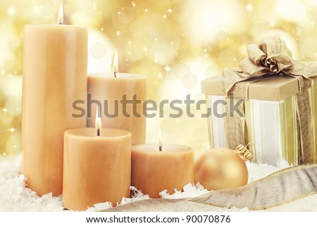 Christmas candle decoration with ornament and gift against an abstract light background. Shallow depth of field.