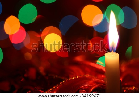 Christmas candle glowing against red ribbons and defocused fairy lights.