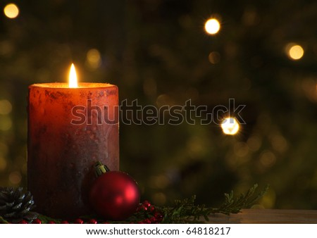 Christmas candle in front of a Christmas tree with sparkling lights and copy space.