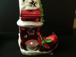 Christmas candle lit inside a decorative flashlight in the form of a red shiny Santaclaus boot, on a black background.