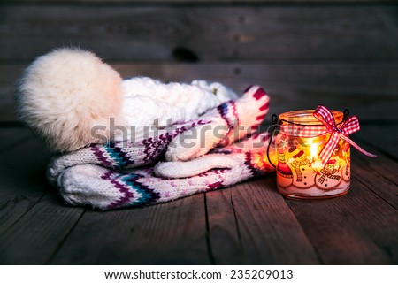 Christmas candle on vintage wooden background. Snowman on snow. Festive decorations. Classic gloves with cap