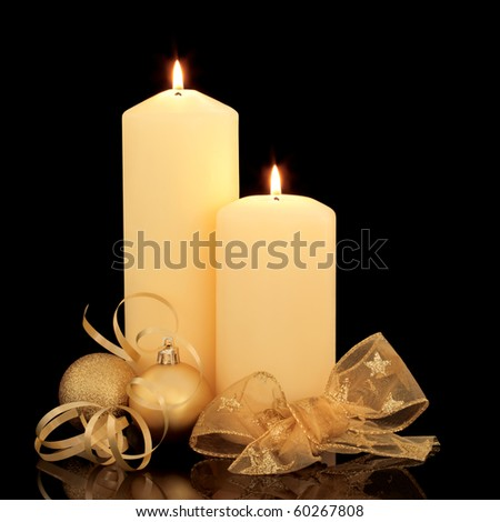 Christmas candle table setting with gold baubles and golden mesh bow and ribbon over black background.