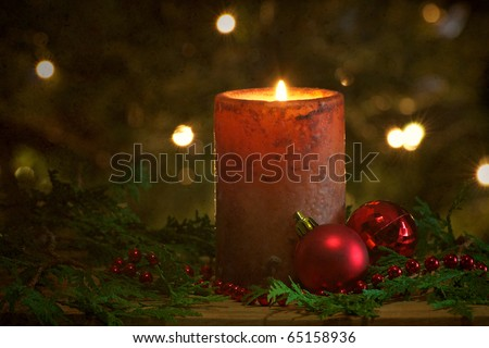 Christmas candle with a light textured background with beads, Christmas balls and cedar sprigs with sparkling lights on the Christmas tree in the background.