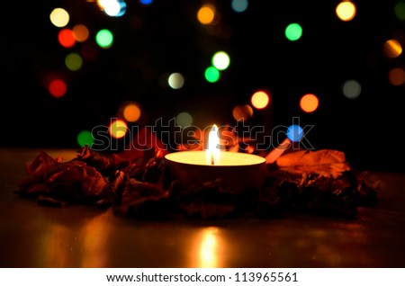 Christmas candle with background of colorful bokeh