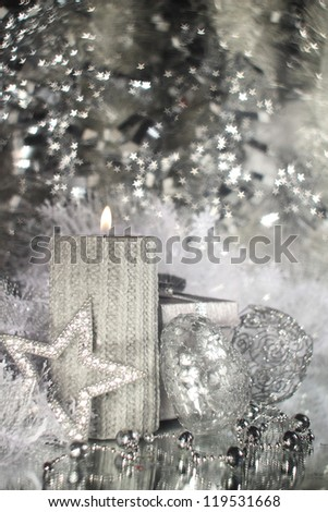 Christmas candle with gift and different silver decoration