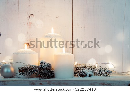 Christmas candles and snowy fir branches over white wooden background with lights #322257413