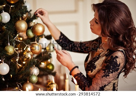 Christmas Candles. Happy Surprised Woman Posing Near Christmas Tree at home.